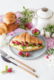 Breakfast with croissants, tea, bananas, confiture, cheese and berries on white background