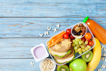 School lunch box with vegetables, fruits and sandwich for healthy snack on turquoise wooden table top view. © juliasudnitskaya