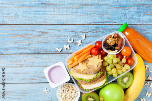 School lunch box with vegetables, fruits and sandwich for healthy snack on turquoise wooden table top view.