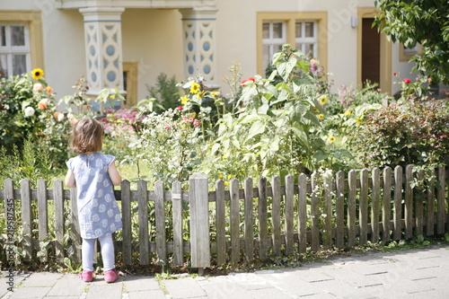 Leinwanddruck Bild Mädchen steht vor Gartenzaun