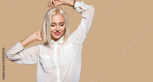 Fototapeta Attractive girl in white shirt dancing. Young woman having fun, beige wall on background. Studio portrait of beautiful blonde hair model. Concept of party and fun.