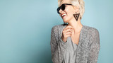 Happy joyful blonde in stylish casual clothes. Engaging lovely female with short fair hair in sunglasses. Isolated on blue background