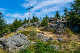 Summit Cross on top of a mountain in the bavarian forest with trees and rocks and clouds in the background
