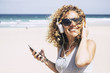 cheerful attractive beautiful caucasian middle age woman smiling at the beach in tropical place while listen music with the smart phone. people enjoying vacation and freedom from work holiday