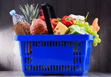 Plastic shopping basket with assorted grocery products