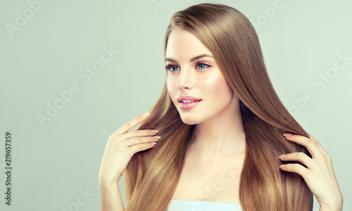 Beautiful model girl with shiny blonde straight long hair . Care and hair products .