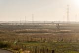 Diesige Landschaft in Andalusien - Stromleitung vor Bergen und eine Koppel im Vordergrund - 219660940