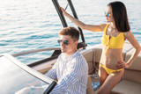 Cute married couple having their honeymoon trip on a luxury sailing boat at summer Carribean Sea. Husband sitting at steering wheel and his loving young wife in yellow bikini standing behind - 219664789