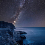 Vibrant Milky Way composite image over landscape of long exposure waves crashing onto rocks - 219674155