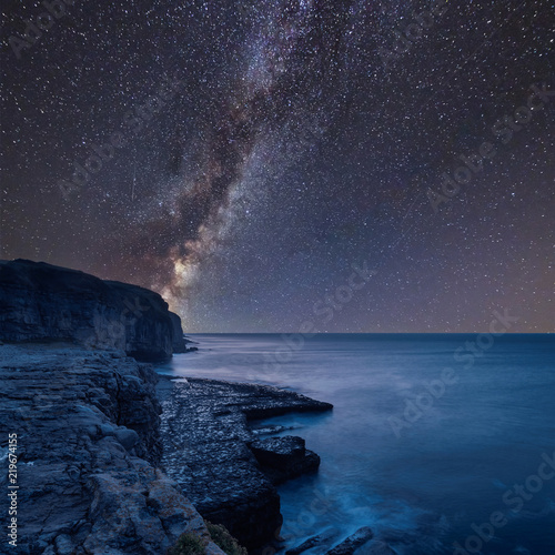 Vibrant Milky Way composite image over landscape of long exposure waves crashing onto rocks