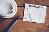 Goals for 2019 word on paper with pen and coffee cup on wooden table. Business concept. - 219681114