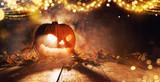Spooky halloween pumpkin on wooden planks in dark cellar. - 219682541