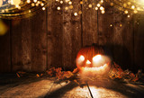 Spooky halloween pumpkin on wooden planks in dark cellar. - 219682550