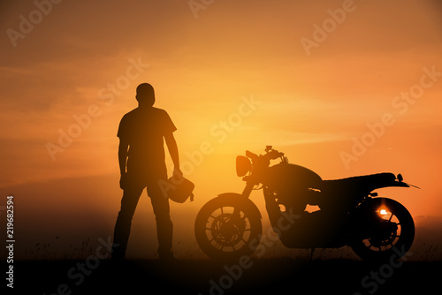 Silhouette of Biker or Rider,motorbike parking with sunset background in Thailand.Young Traveller man standing and holding helmet beside motorcycle.Trip and lifestyle of motorbike concept