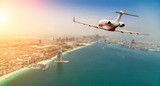 Private jet plane flying above Dubai city in beautiful sunset light. - 219683328