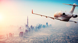 Private jet plane flying above Dubai city in beautiful sunset light. - 219683342