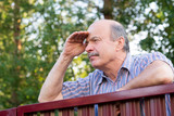 Mature caucasian man carefully watching over the fence. - 219688945