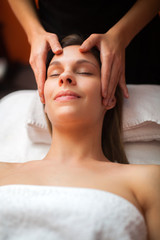 Young woman getting a head massage in a spa