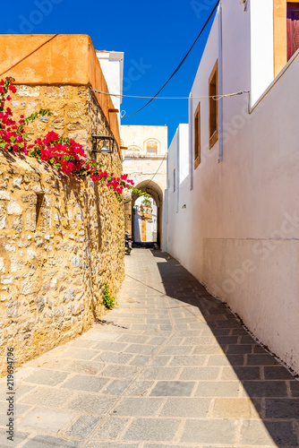 Narrow street with spring flowers on Rhodes island. Lindos village, Dodecanese, Greece.