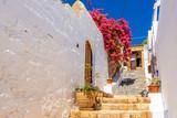 Beautiful Greek street with summer flowers in Lindos village. Rhodes island. Greece. - 219695340