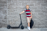 School boy in standing with his electric scooter in the city with backpack - 219696139
