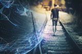 Back view of a blurry man walks down the railway tracks with futuristic computer cyberspace sphere background. - 219708158