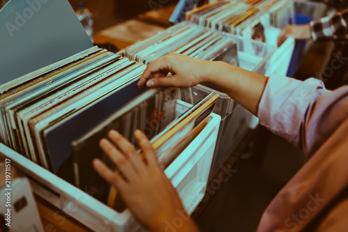 Woman is choosing a vinyl record in a musical store - 219711517