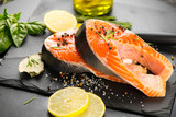 Salmon. Raw trout fish steak with herbs and lemon on black slate background. Cooking, seafood. Healthy eating concept - 219716151