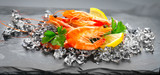 Shrimps. Fresh prawns on a black background. Seafood on crashed ice with herbs. Healthy food, cooking - 219716376