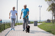 Full length portrait of active senior couple enjoying morning run with pet dog on park, copy space