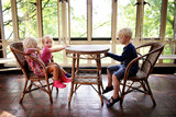 Three Little Children Sitting at an Old Bistro Table in a Sunroom Waiting for Food - 219735953