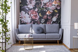 Sunlit, gray sofa by a floral print wall in the nook of a feminine living room interior with golden accessories - 219740762