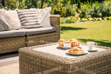 Beige color wicker table and settee on a porch during sunny afternoon in the garden. Croissants and coffee served on the table. - 219740925