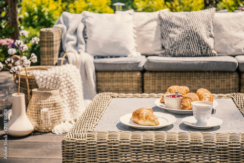Leinwanddruck Bild An outdoor wicker table and a sofa with cushions. Croissants for breakfast on a patio on a summer morning in an exclusive apartment with garden during vacation.