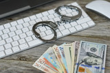 Money from online fraud concept, with cash banknotes near computer keyboard and handcuffs  - 219755109