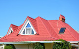 Valley and gable roofing construction with attic windows,  rain gutter, waterproofing. Roof gutter system, skylight window on attic house metal tiles roofing. - 219758347
