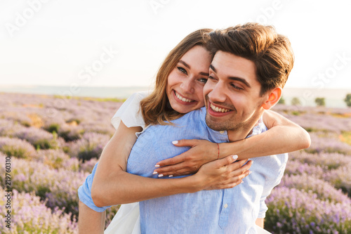 Foto Murales Joyful young couple having fun at the lavender field together