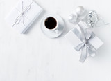 Christmas present, ornaments and a cup of coffee on white painted wooden background. Symbolic image. Flatlay. Copy space - 219767521