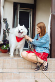 For a walk. Stylish blonde-haired woman wearing nice black sandals taking her husky for a walk - 219770337