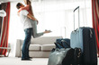 Suitcases prepared for vacation, happy couple hugs