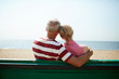 Back view of senior affectionate couple sitting on bench by waterside on hot summer day