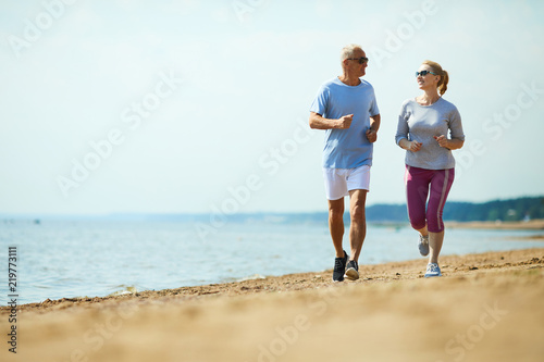 Leinwanddruck Bild Active senior man and woman running down sandy beach with waterside on background