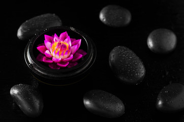 Close up of spa soap with water lilly flower shape on black background with stones and water drops © Mybona