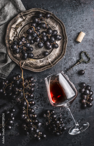 Fototapeta Red wine concept with glass, grapes in old plate and vintage corkscrew on dark table background, top view