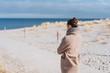 canvas print picture - frau macht einen spaziergang durch die dünen im winter