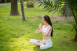 Young yoga woman meditating at the city park with tropical plants on summer weekend morning time. Words of gratitude and admiration to the Lord.