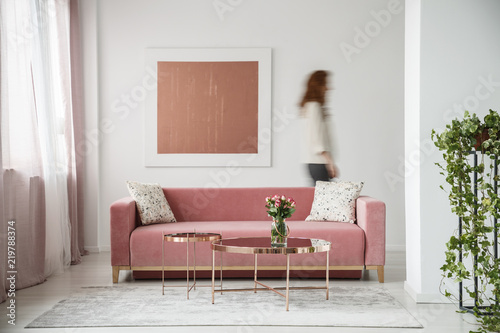 Leinwanddruck Bild Blurred person against the wall with painting in white flat interior with plant and millenial pink couch. Real photo
