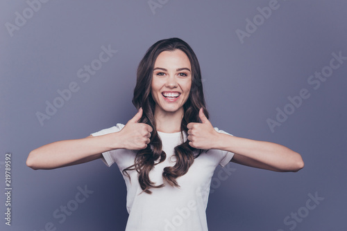 Leinwandbild Motiv Portrait of attractive pretty charming adorable stylish cheerful curly-haired girl in casual white t-shirt, showing double thumbs-up, isolated over grey background