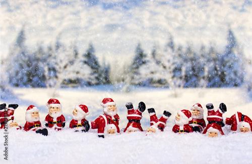 Leinwanddruck Bild Weihnachtsmänner vor Winterlandschaft