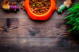 dry cat food in bowl on wooden background top view